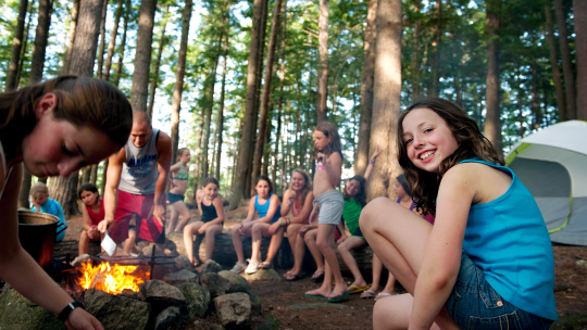 girls hanging out around a campfire