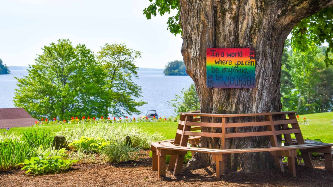 Rainbow inspirational quote sign on tree overlooking camp lake
