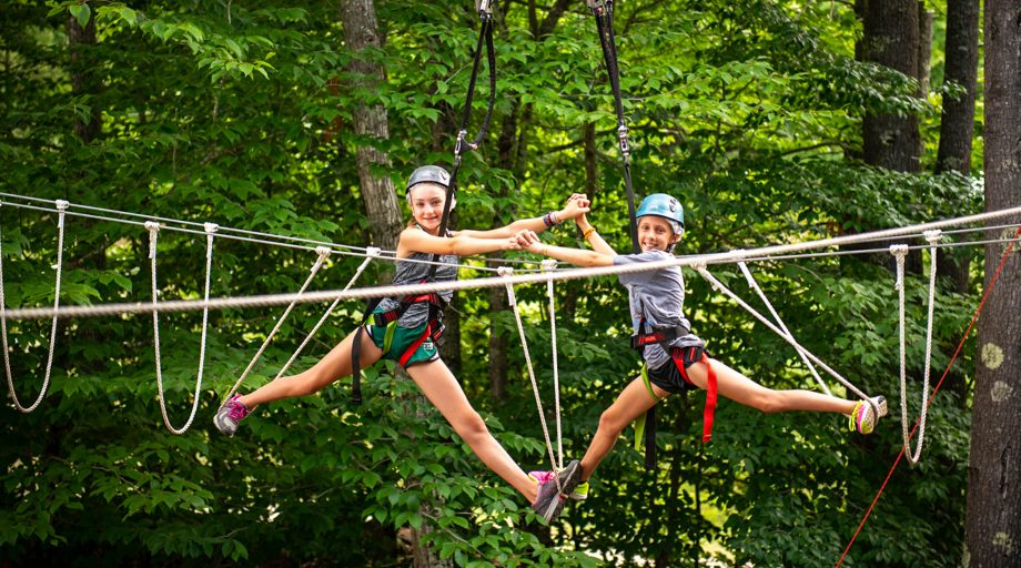 two girls holding hands while doing splits on a ropes course
