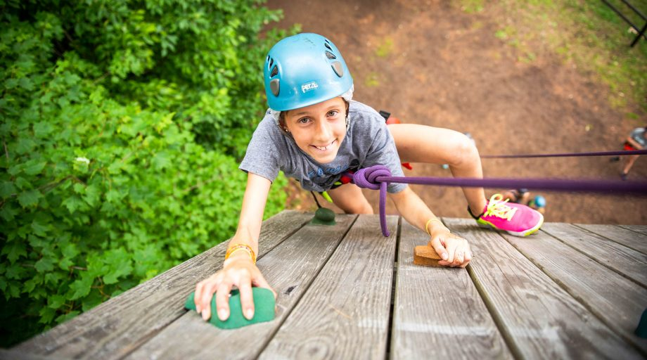 a girl smiling while she climbs a rock wall