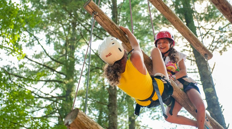 two girls traversing a high ropes course