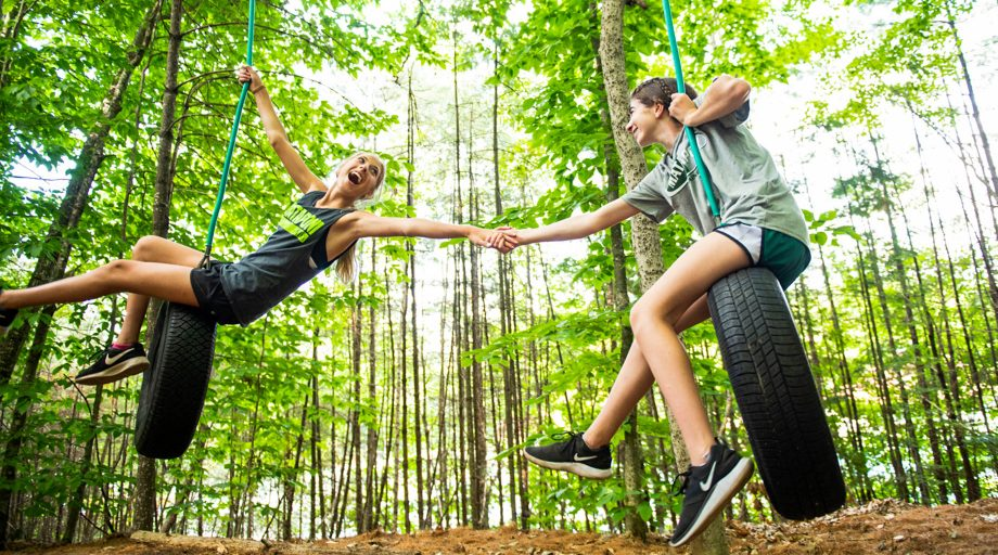 girls holding hands on two separate tire swings