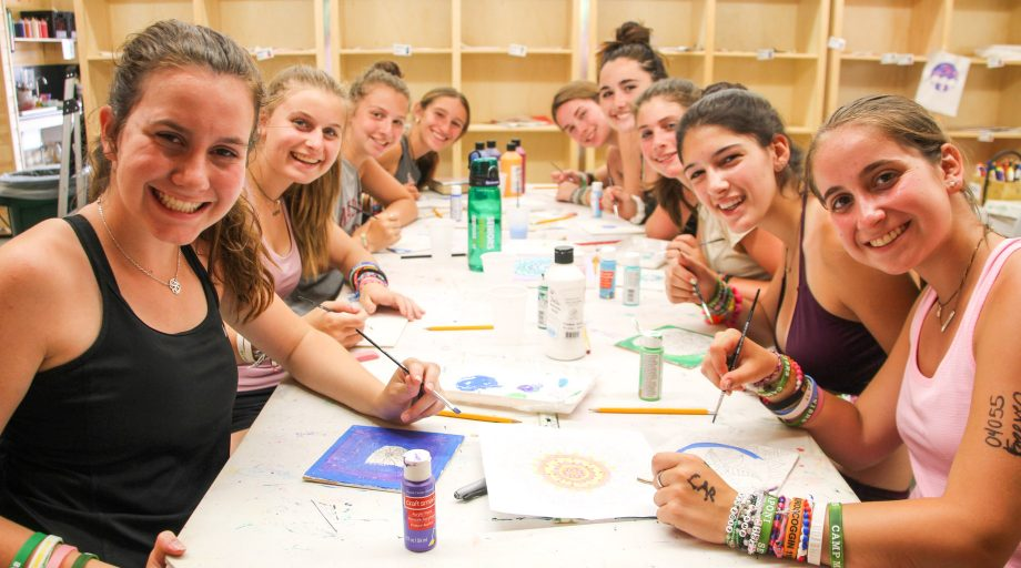 a group of campers working on art together