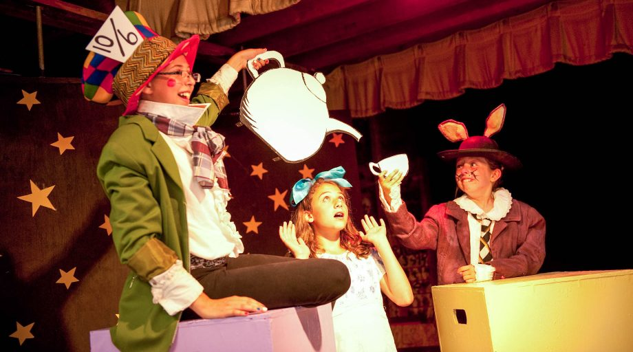 girls putting on a stage production of Alice in Wonderland