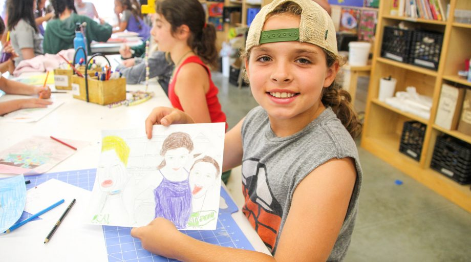 a girl proudly displaying her artwork