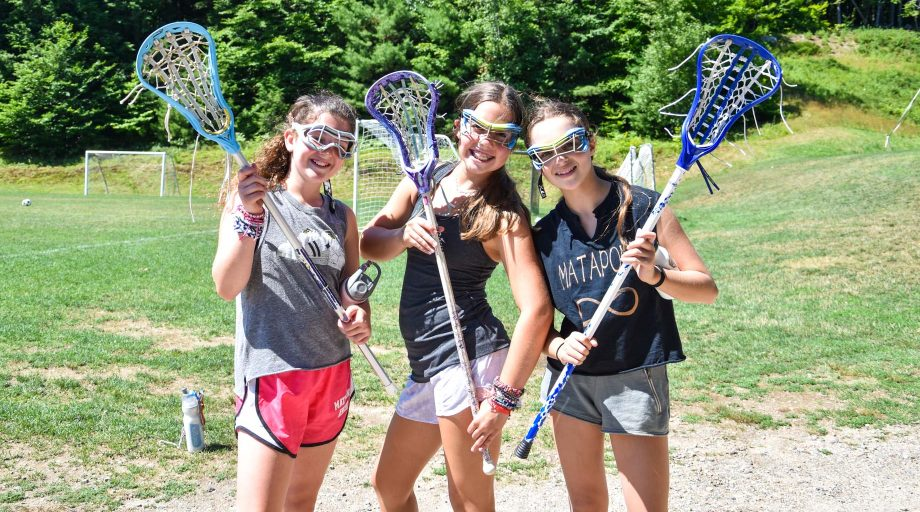 three campers posing with lacrosse sticks