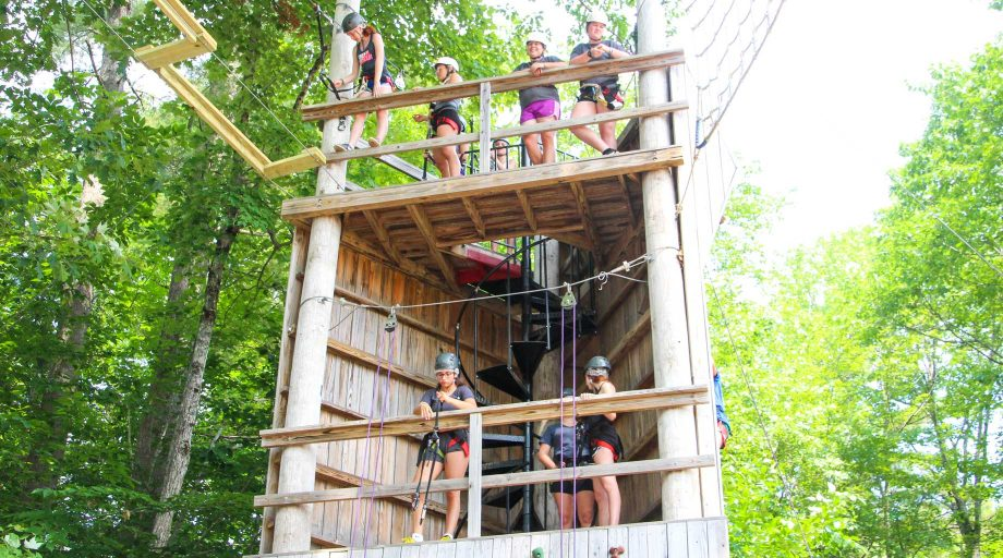 Campers stand on multi-level ropes course structure