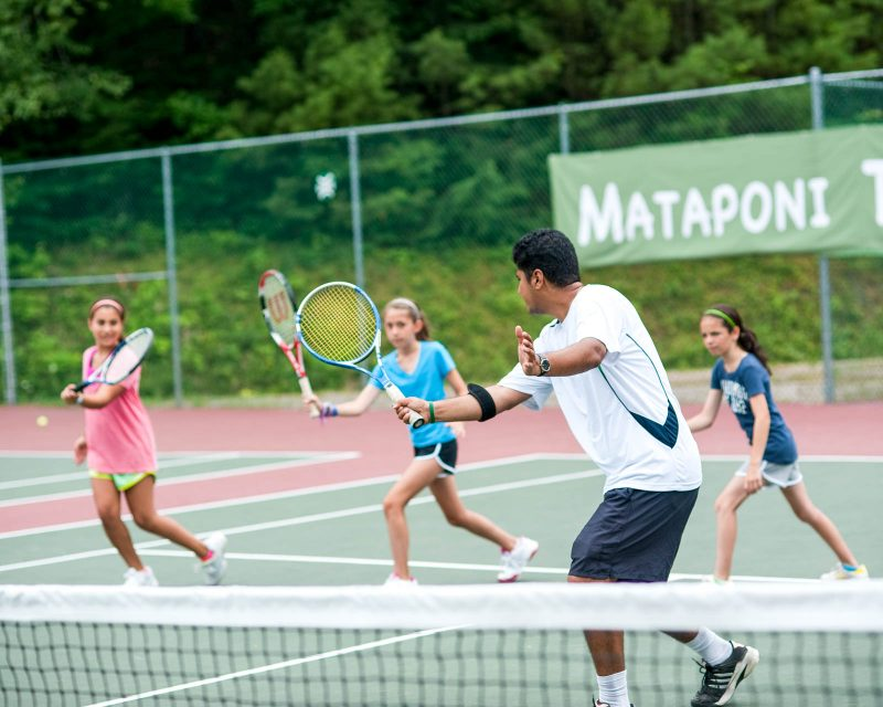 three girls being taught how to play tennis