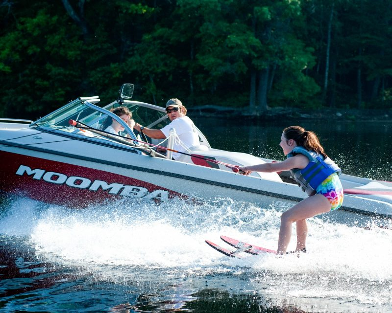 a girl water skiing as two people look on from the boat