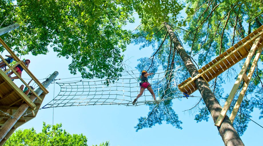a girls traversing the ropes course at Camp Mataponi