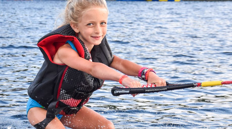Young girl holds boat arm while waterskiing at summer camp