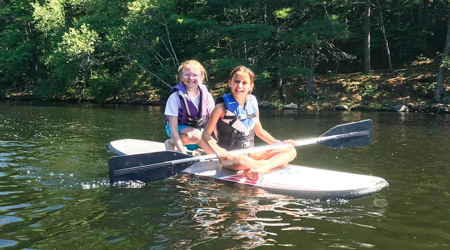 Smiling campers sit on paddleboard