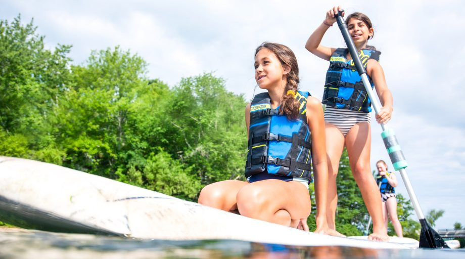 Girls kneels on front of paddleboard while another stands behind