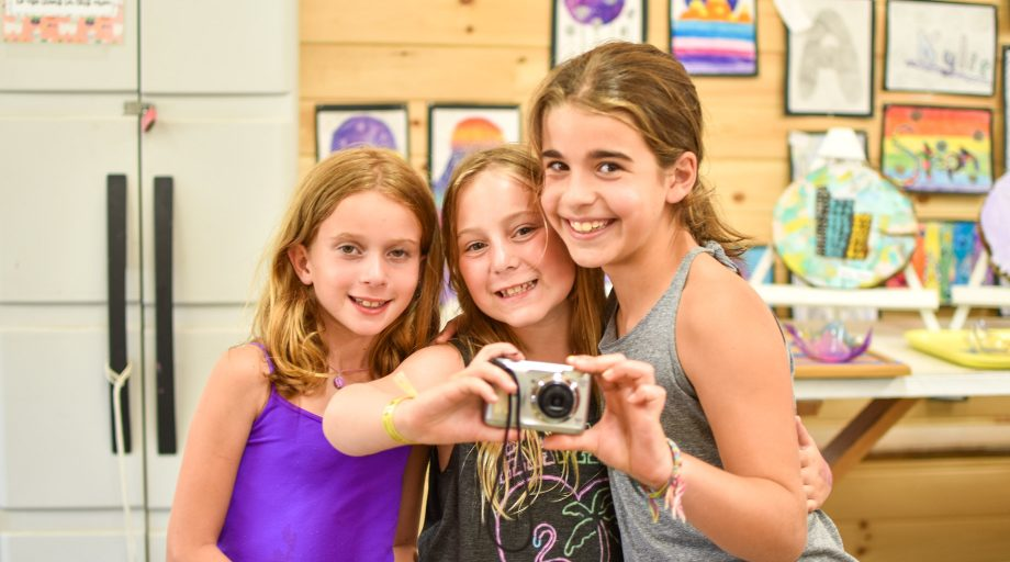 three girls posing while holding a camera