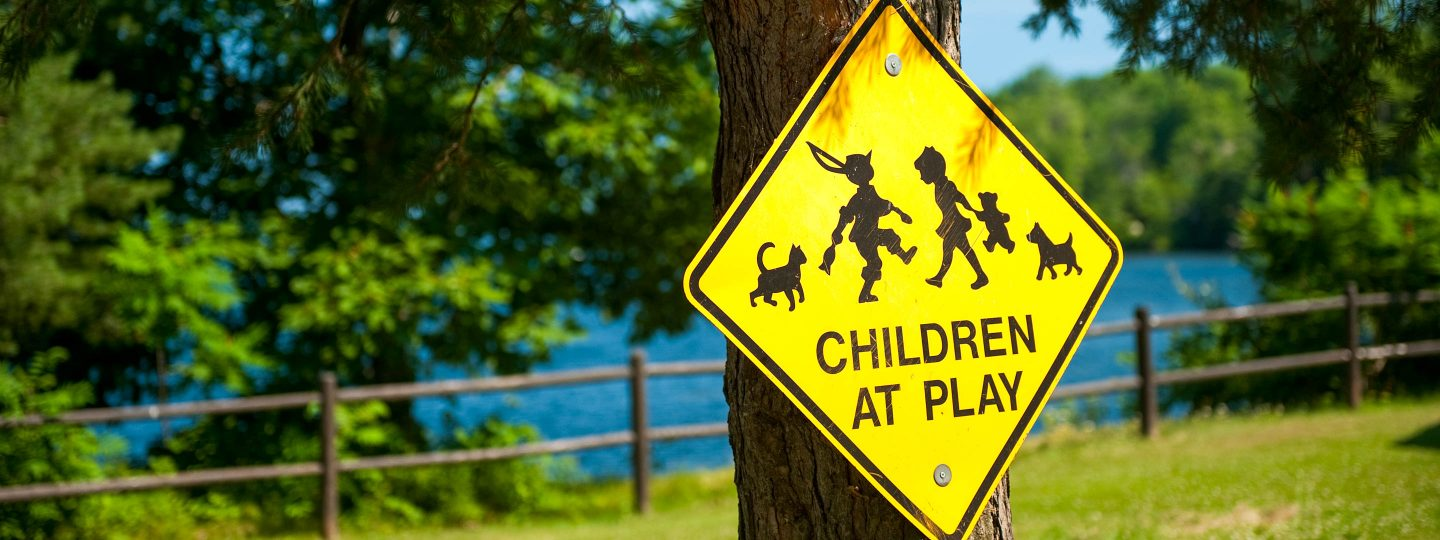 "a yellow sign reading ""children at play"" hanging on a tree"