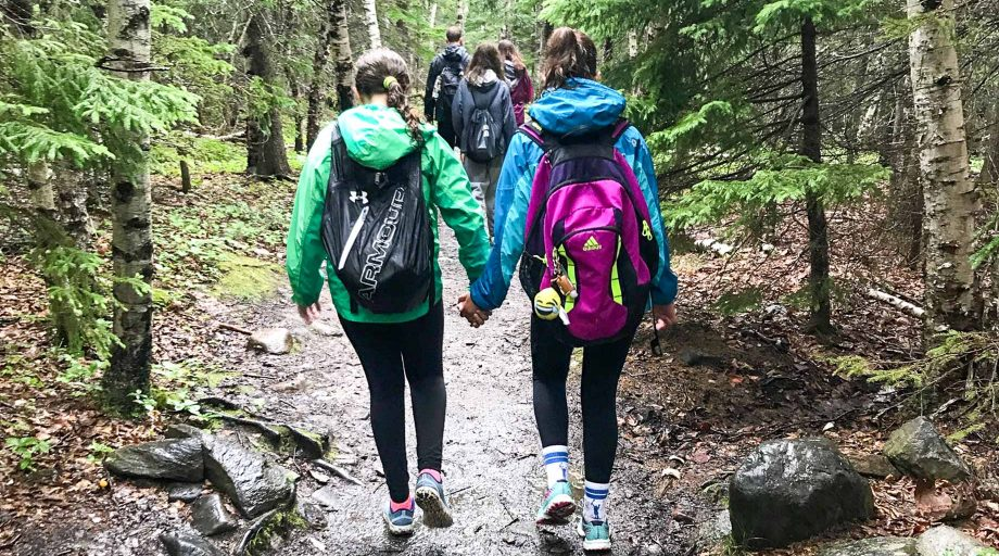 two girls holding hands and hiking