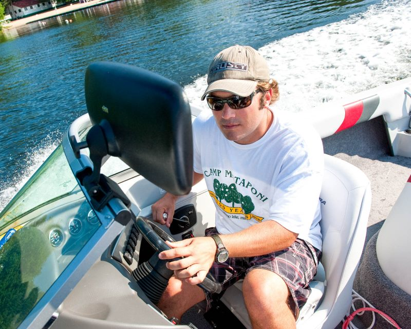 a camp counselor driving a boat on Sebago Lake