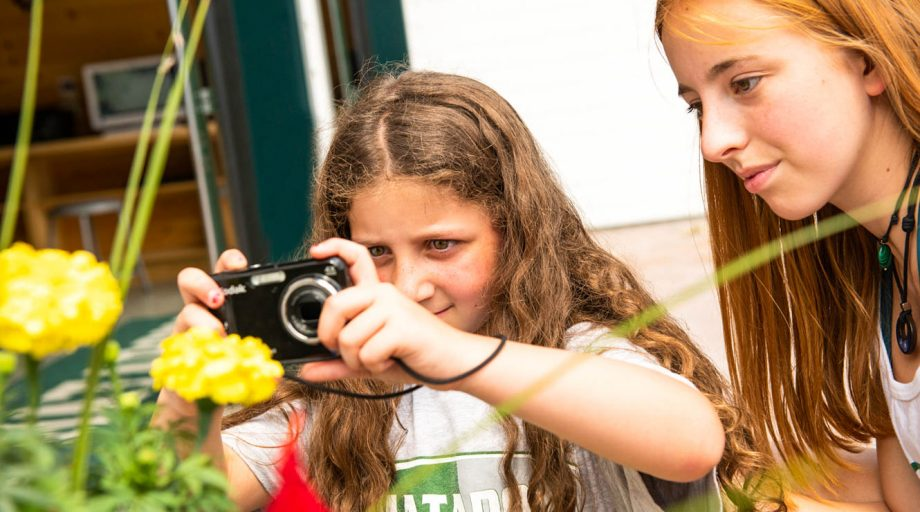 two girls taking a photograph of yellow flowers