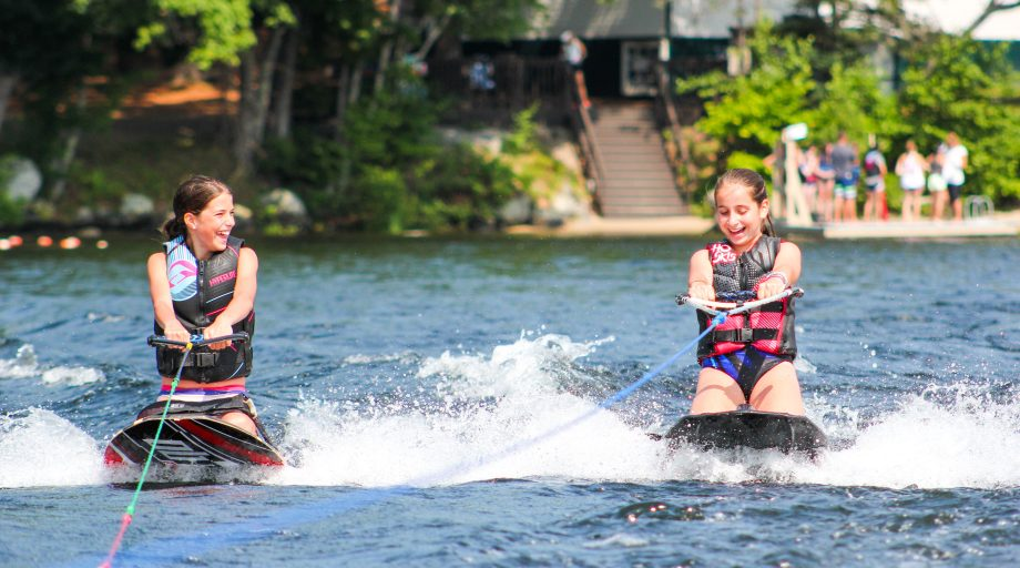 Two girls kneeboarding at summer camp