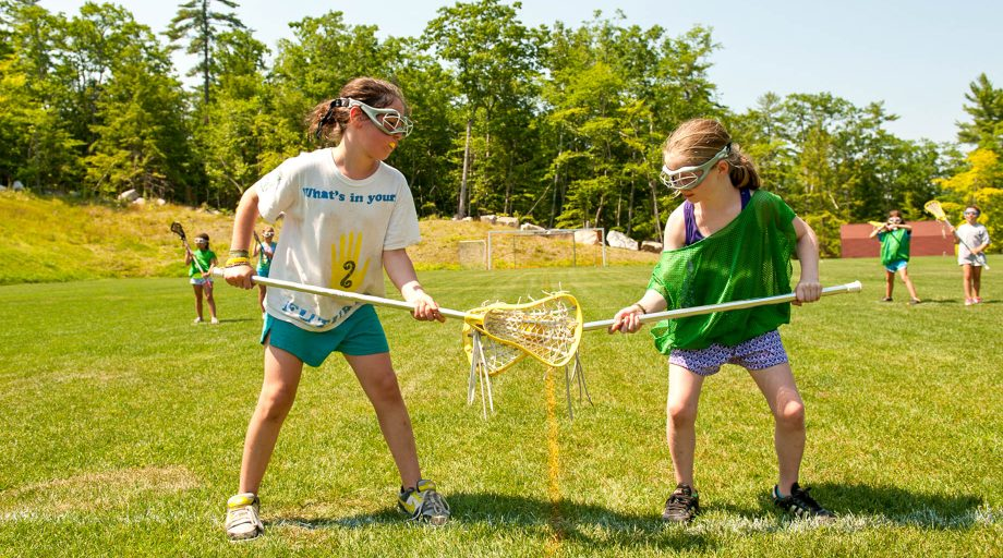 girls facing off with lacrosse sticks