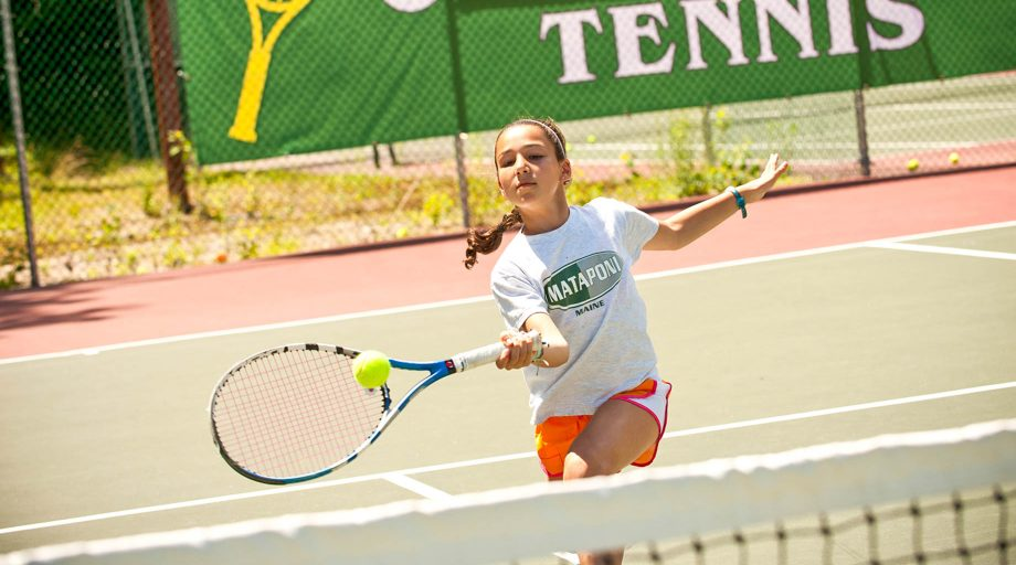 a girl hitting a tennis ball with her racket