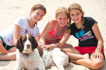 three girls sitting on a beach with a dog