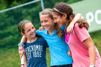 three girls with their arms around each other on the tennis court