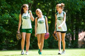 three girls walking together on a softball field