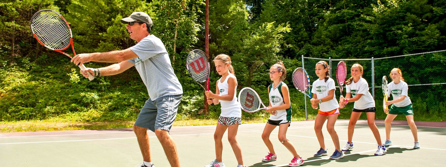 young campers being taught tennis techniques