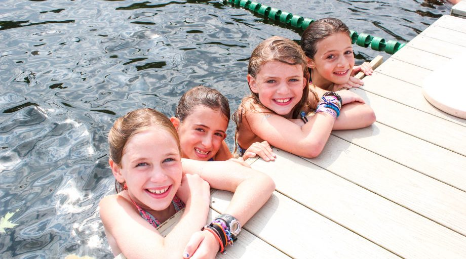 Swimming campers rest elbows on dock