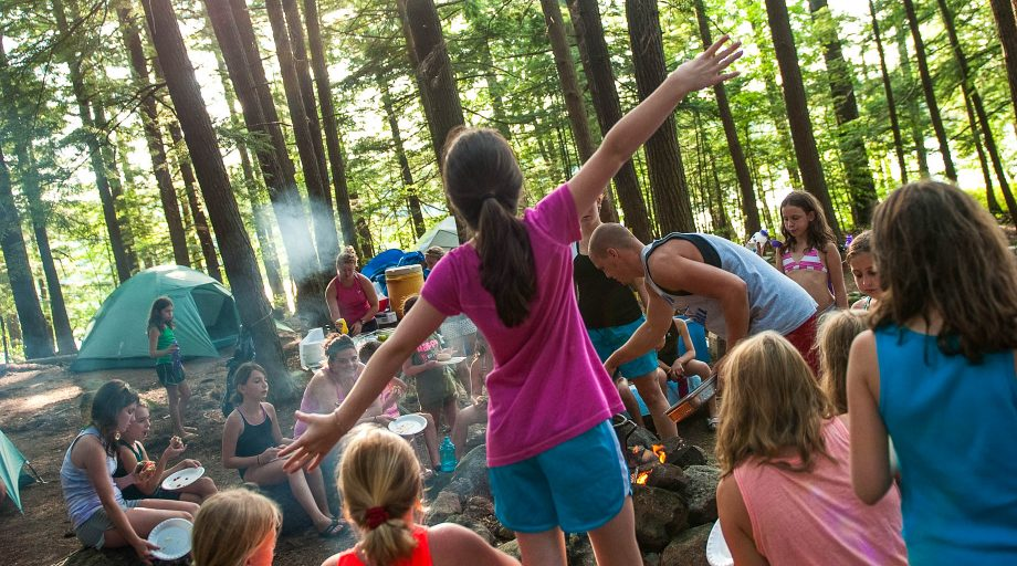 a girl standing with her arms out at a group campfire