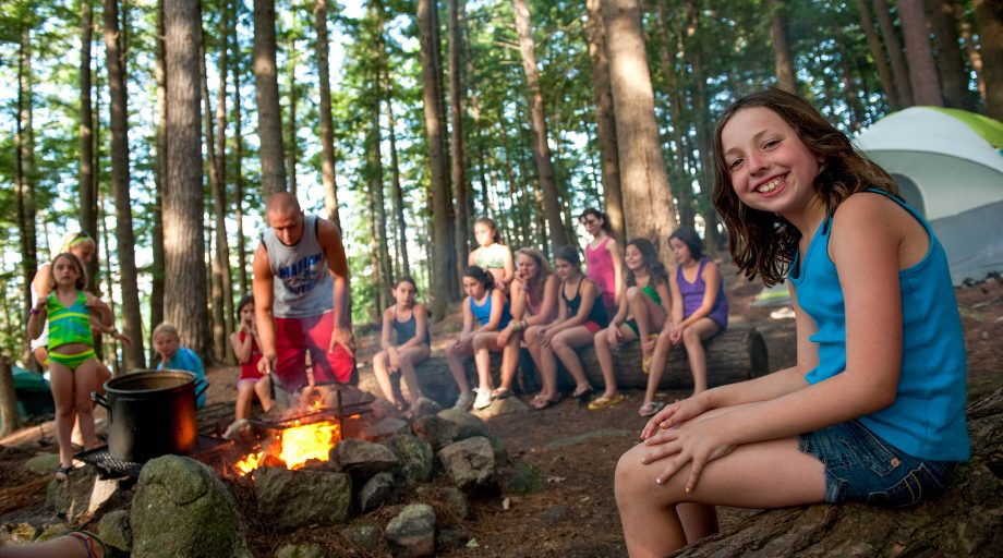 girls smiling while sitting around a camp fire