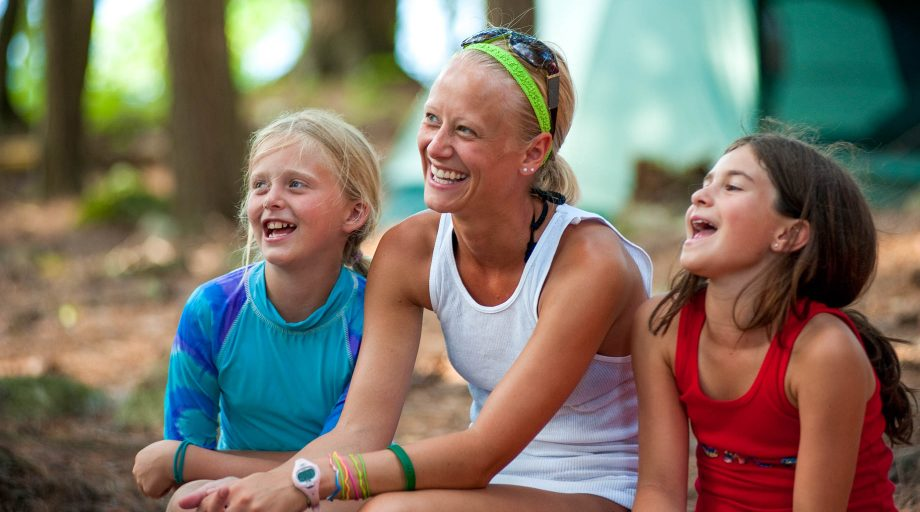 two campers laughing with their camp counselor