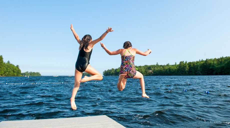two girls jumping off a dock into Sebago Lake