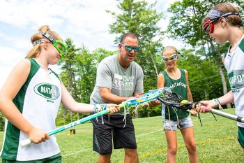 girls learning lacrosse techniques from Dan Isdaner