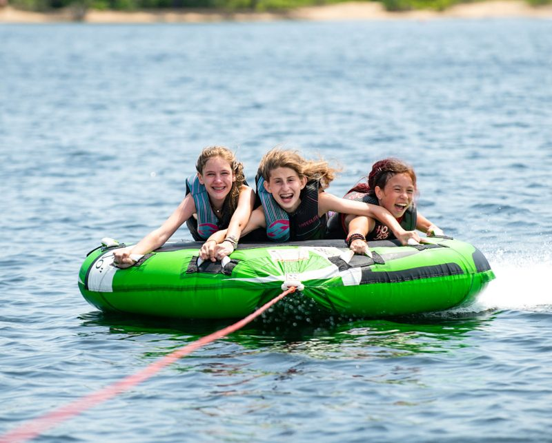 three girls water tubing on a lake
