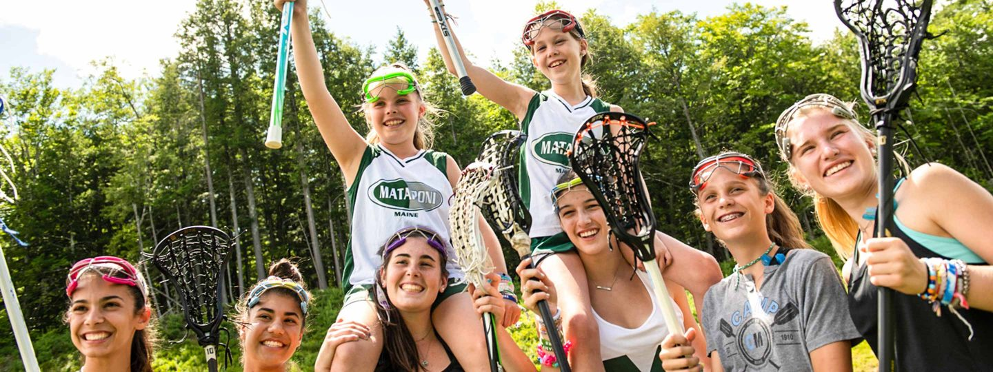 girls posing with their lacrosse sticks