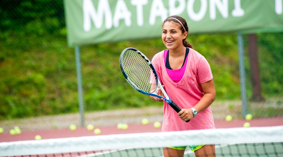a girl smiling on the tennis court