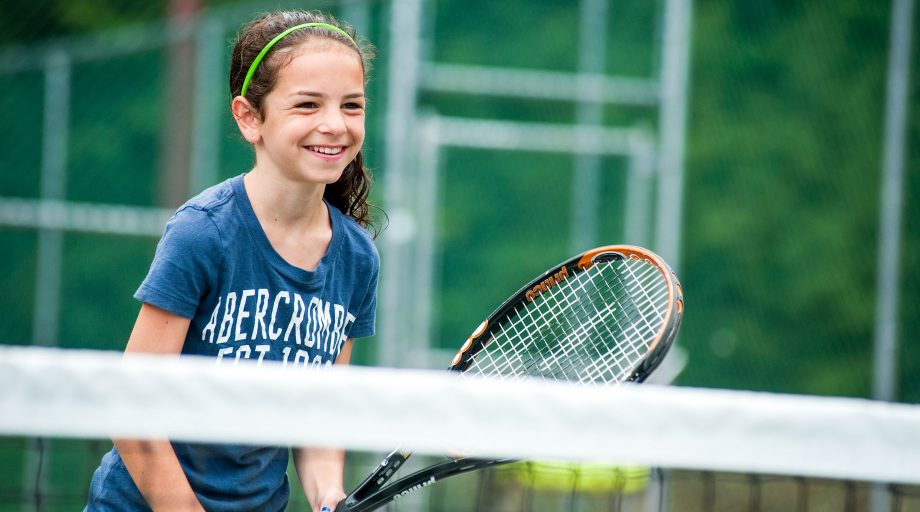 a girl smiling while holding a tennis racket
