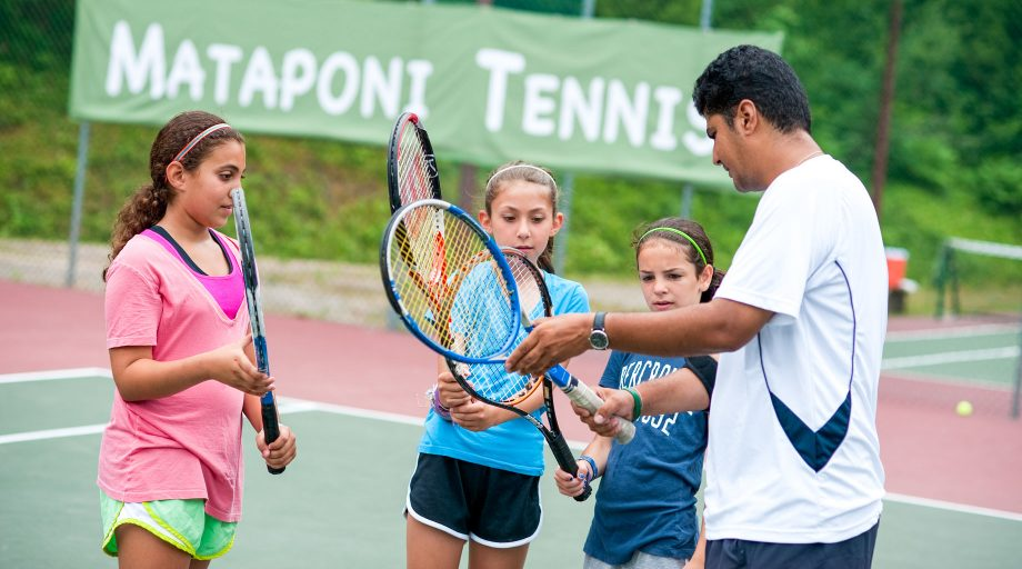 girls being instructed on how to play tennis