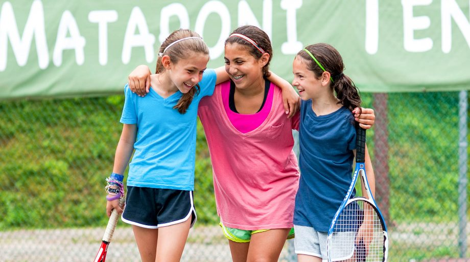 three girls with their arms around each other on a tennis court