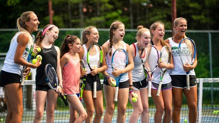 Group of campers laugh on tennis court