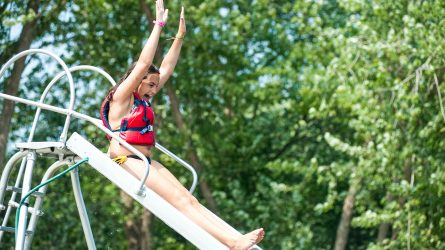 Camper slides down waterslide with arms in the air