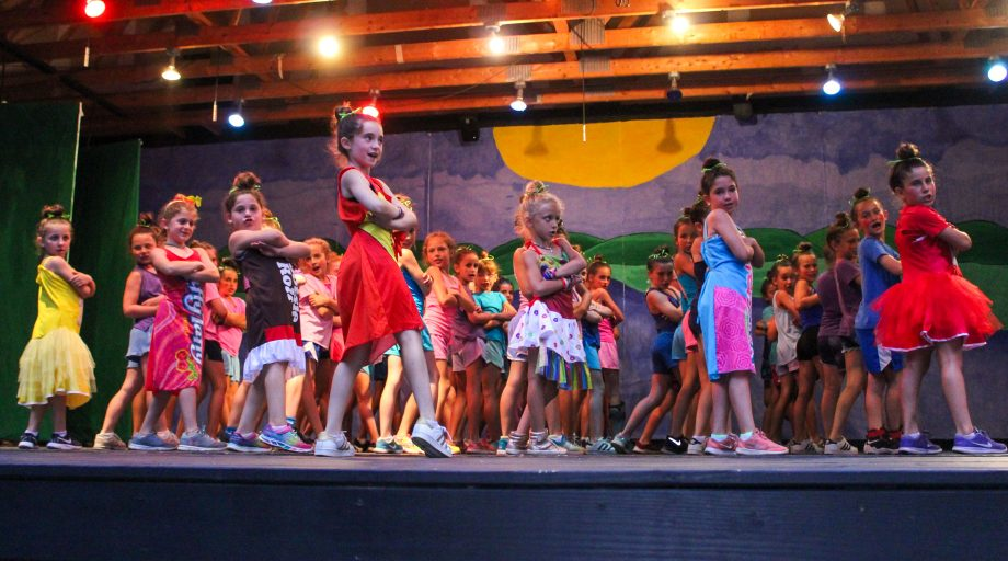 Girls perform in costume at summer camp