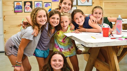 Group of girls pose next to art table at summer camp