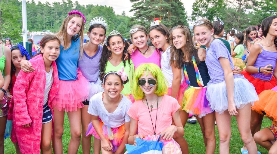 Group of campers pose in colorful costumes