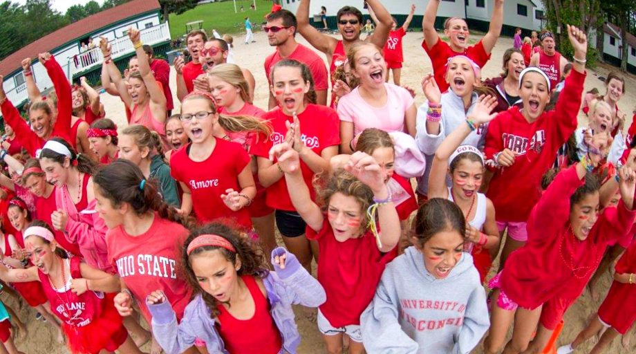 Group of campers wearing red shirts cheer