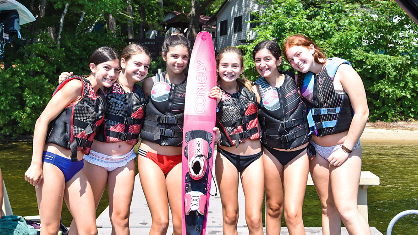 Group stands on dock with waterski
