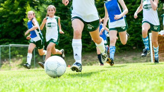 Camper kicks soccer ball in summer camp game