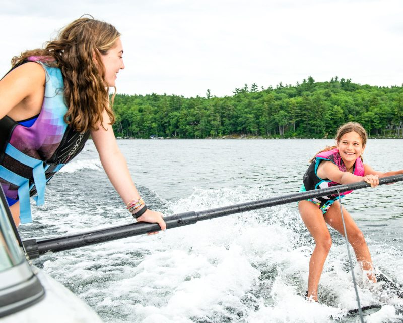 Mataponi staff helps camper waterski
